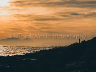 Strand coast of rocks and man standing at sunset